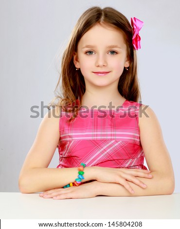 Smiling portrait of Girl Sitting at a Desk, Isolated, White - stock photo