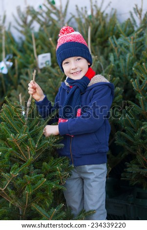 smiling positive boy buying christmas tree at outdoor marker at winter - stock photo