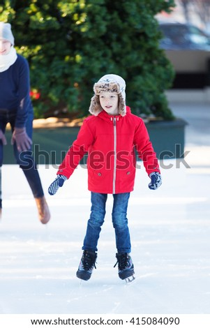 smiling positive boy enjoying ice skating at outdoor skating rink, winter holiday or vacation activity - stock photo