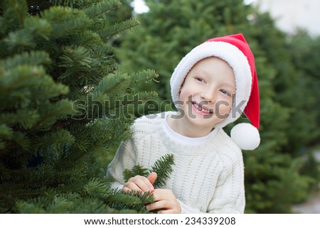 smiling positive boy in santa hat buying christmas tree at outdoor marker at winter - stock photo