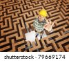 smiling positive worker in 3d maze - stock photo