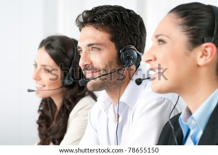 Smiling positive young man with headset and colleagues in a modern call center office - stock photo