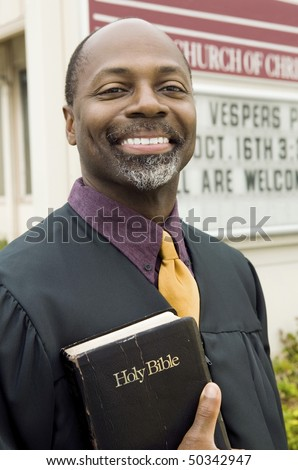 Smiling Preacher in Front of Church, portrait - stock photo