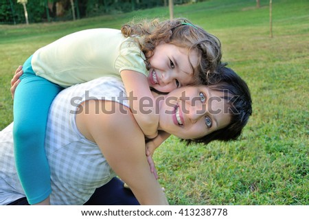 Smiling pregnant mother carrying her cute daughter on her back in the city park - stock photo