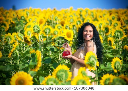 Smiling pregnant woman in sunflowers - stock photo