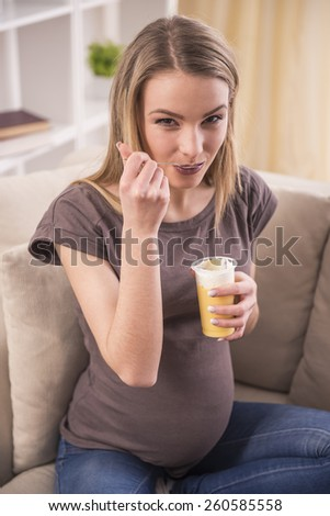 Smiling pregnant woman is eating  while is sitting on the couch.