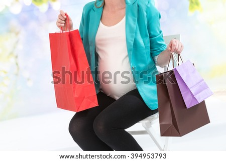 Smiling pregnant woman sitting with shopping bags