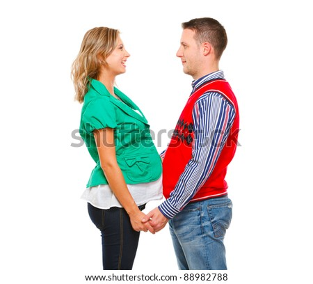 Smiling pregnant woman with husband looking on each other isolated on white - stock photo