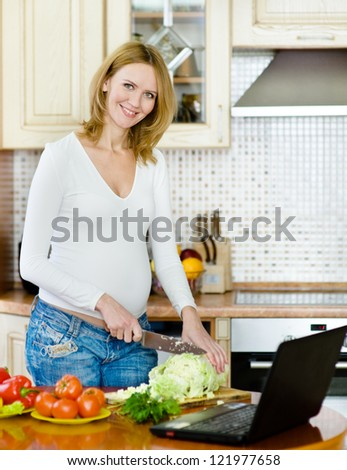 smiling pregnant woman with laptop on kitchen - stock photo