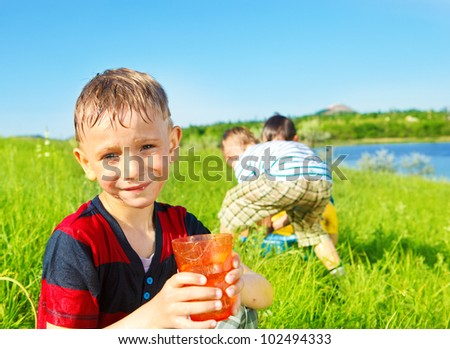 Smiling preschool boy holding water in glass