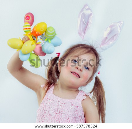 Smiling preschool kid with Easter bunny ears on holding a bunch of colorful eggs - stock photo