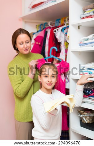 Smiling preschooler girl with mom choosing apparel in cloakroom
