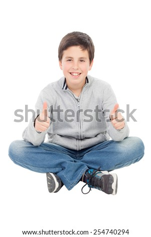 Smiling preteen boy sitting on the floor saying Ok isolated on a white background