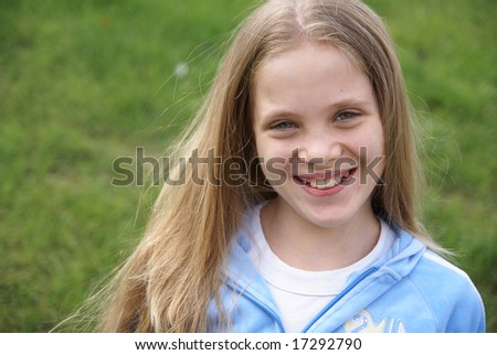Smiling preteen girl outdoors on green grass background