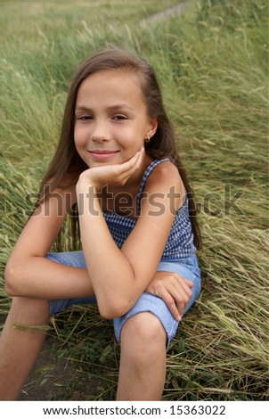 Smiling preteen girl sitting on grass