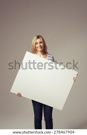 Smiling Pretty Blond Girl Holding an Empty White Sign Board, Emphasizing Copy Space, and Looking at the Camera. Captured in Studio with Brown Background.