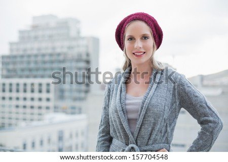 Smiling pretty blonde posing outdoors on urban background - stock photo