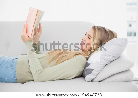 Smiling pretty blonde reading book lying on cosy sofa in bright living room