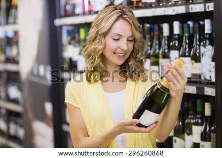 Smiling pretty blonde woman looking at wine bottle in supermarket - stock photo
