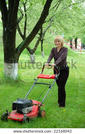 Smiling pretty blonde woman moving a lawn mower, mowing fresh green grass