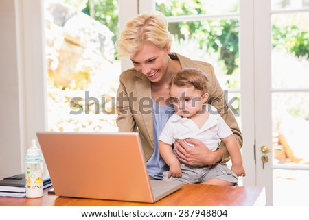 Smiling pretty blonde woman using laptop with his son in the office - stock photo