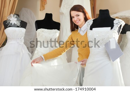 Smiling pretty bride chooses wedding gown at bridal boutique - stock photo