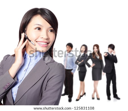 Smiling pretty business woman with headset. Smiling call center executive with colleagues in blur background isolated on white background, asian model - stock photo