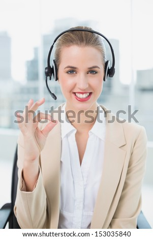 Smiling pretty call center agent in bright office giving okay gesture