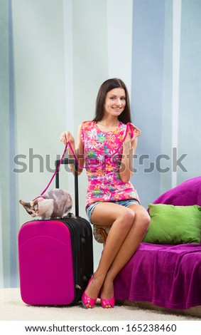 Smiling pretty girl going on vacation with her cat - stock photo