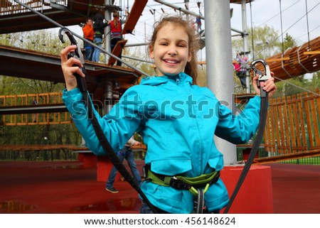 Smiling pretty girl holds safety rope near Rope way on special playground - stock photo