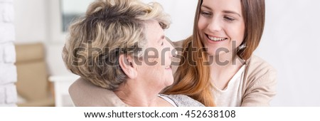 Smiling pretty girl hugging her happy loving grandmother