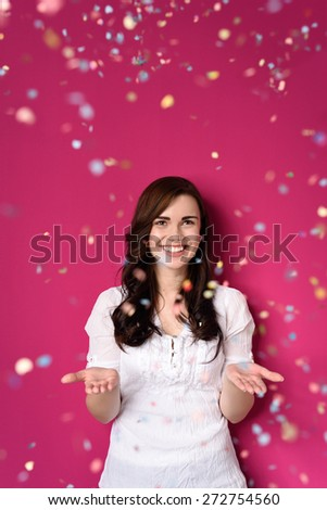 Smiling Pretty Girl in White Shirt Opening her Both Hands on a Shower of Confetti, Isolated on Pink Background. - stock photo