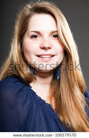 Smiling pretty girl with long brown hair isolated on dark background. Studio fashion shot.
