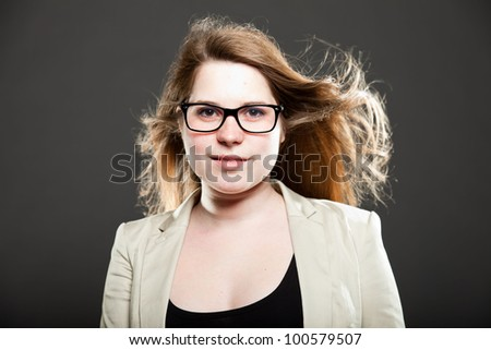 Smiling pretty girl with long brown hair isolated on dark background. Studio fashion shot. Wearing glasses.