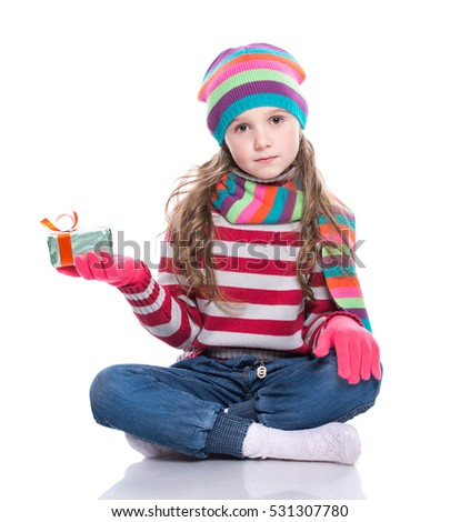 Smiling pretty little girl wearing colorful knitted scarf, hat and gloves, holding christmas gift isolated on white background