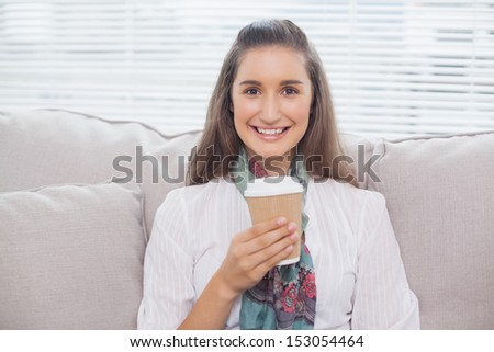 Smiling pretty model holding mug of coffee sitting on cozy sofa