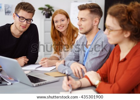 Smiling pretty red haired young woman sitting with coworkers around laptop at work during meeting