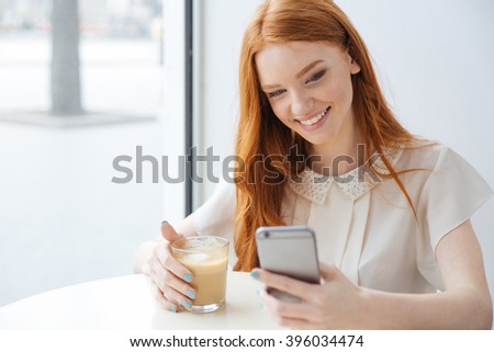 Smiling pretty redhead young woman sitting in cafe and using cell phone