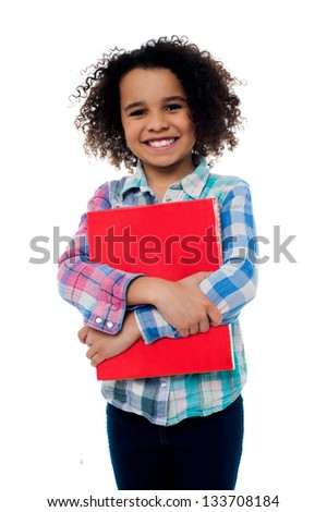 Smiling pretty school kid embracing a notebook. - stock photo