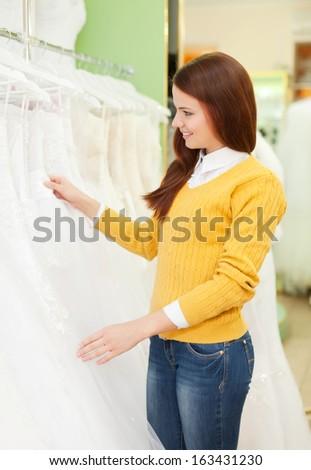 Smiling pretty woman chooses white dress at shop of wedding fashion - stock photo