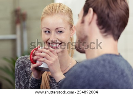Smiling pretty woman drinking coffee as she chats with her husband smiling happily at him over the rim of the mug - stock photo