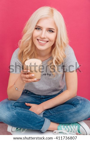 Smiling pretty woman holding glass with cappuccino over pink background
