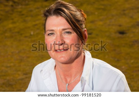 Smiling pretty woman middle aged enjoying outdoors. Clear sunny spring day with blue sky. - stock photo