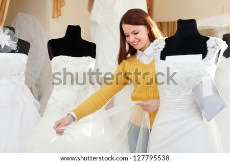 Smiling pretty woman shopping for wedding outfit in bridal boutique - stock photo