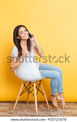 Smiling pretty woman sitting on the chair and talking on the phone over yellow background - stock photo