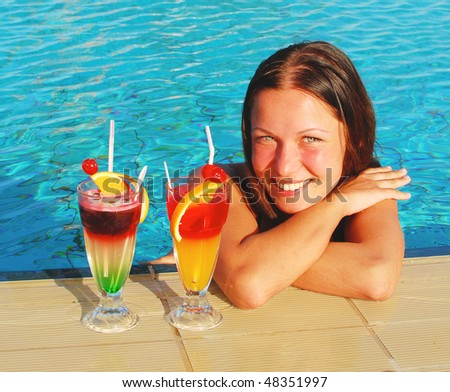 smiling pretty woman with cocktails in the pool