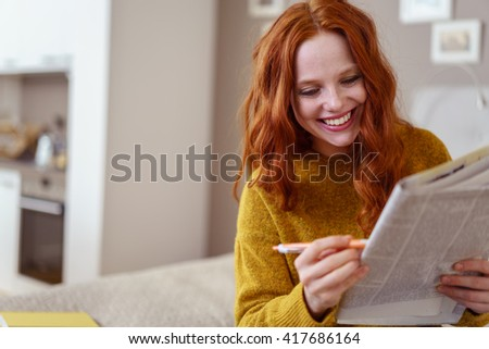 Smiling pretty woman with long red hair and yellow sweater checking help wanted advertisements in newspaper while sitting on bed with mobile phone - stock photo