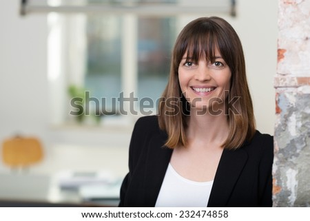 Smiling Pretty Young Businesswoman in Black and White Coat Leaning on Vintage Wall. Captured Indoor. - stock photo