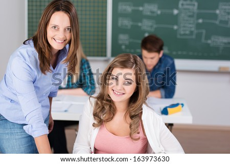 Smiling pretty young teenage girl sitting in class with her attractive middle-aged female teacher bending over the desk assisting her - stock photo