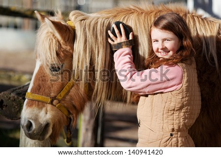 Smiling pretty young teenage girl standing grooming the mane of her horse with a brush in the sunshine in an outdoor paddock - stock photo